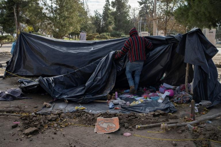 A Mexican man breaks down his campsite in a park in Ciudad Juarez not far from the bridge over the Rio Grande