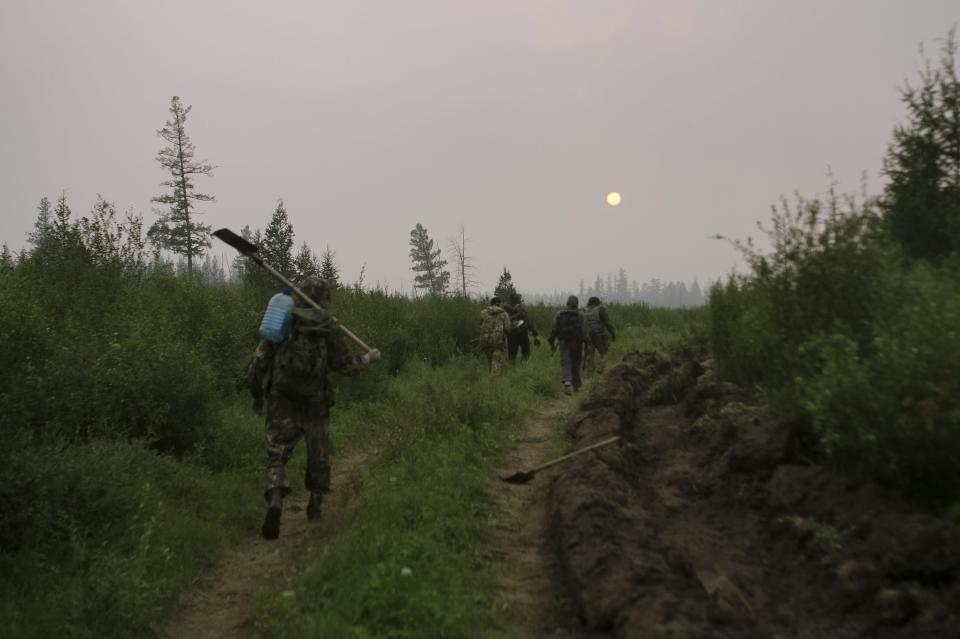 Members of volunteers crew walk to their camp after battle the fire at Gorny Ulus area west of Yakutsk, Russia, Thursday, July 22, 2021. The hardest hit area is the Sakha Republic, also known as Yakutia, in the far northeast of Russia, about 5,000 kilometers (3,200 miles) from Moscow. About 85% of all of Russia's fires are in the republic, and heavy smoke forced a temporary closure of the airport in the regional capital of Yakutsk, a city of about 280,000 people. (AP Photo/Ivan Nikiforov)