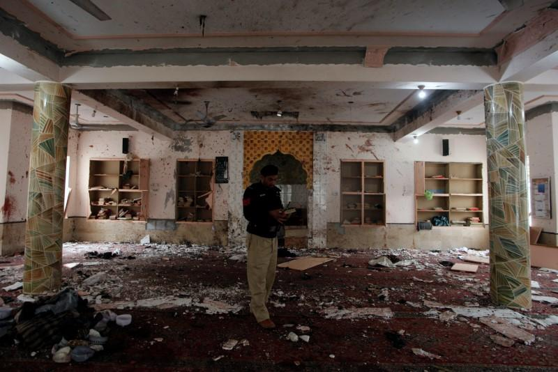 A police officer stands amidst the damages as he is surveying and collecting evidence from the site of a bomb blast in a mosque in Quetta,