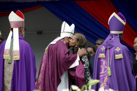 A priest who officiated the funeral of Haiti's former President Rene Preval embraces former First Lady Elisabeth D. Preval at the end of the religious ceremony in Port-au-Prince, Haiti, March 11, 2017. REUTERS/Andres Martinez Casares