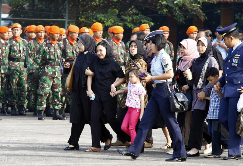 Family members and relatives of victims in an Indonesian air force plane crash prepare to leave for Yogyakarta at Halim Perdanakusuma air base in Jakarta, Indonesia, Friday, June 22, 2012. The Fokker F-27 turboprop plane crashed into the military housing complex in the capital Thursday during a routine training flight, killing at least eleven people. The bodies of some victims were flown to Yogyakarta to be delivered to the hometowns for burial. (AP Photo/Achmad Ibrahim)
