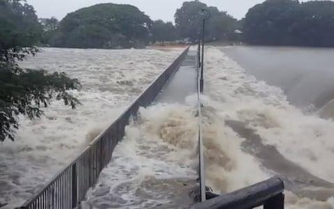 Floodwater flows over the Aplins Weir Rotary Park footbridge in Mundingburra district, Townsville - Credit: Reuters