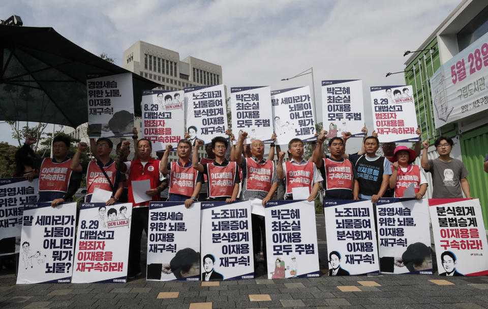 """In this Aug. 29, 2019, photo, South Korean protesters shout slogans during a rally near the Supreme Court of Korea in Seoul, South Korea. The letters read """" Arrest, Lee Jae-yong."""" (AP Photo/Lee Jin-man)"""