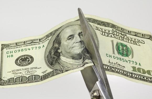 Scissors cutting through a $100 bill.