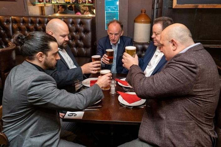 Cheers! Some drinkers in London hail the return of indoor service