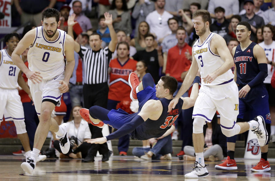 Liberty forward Scottie James (31) falls after colliding with Lipscomb forward Rob Marberry (0) in the second half of the Atlantic Sun NCAA college basketball tournament championship game Sunday, March 10, 2019, in Nashville, Tenn. Liberty won 74-68. (AP Photo/Mark Humphrey)