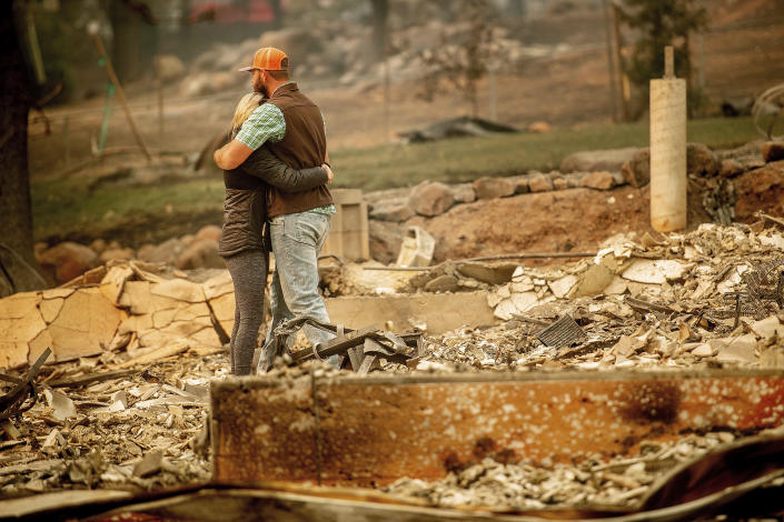 <p>Chris and Nancy Brown embrace while searching through the remains of their home, leveled by the Camp Fire, in Paradise, Calif., on Monday. As the fire approached, Nancy Brown escaped from the home with her 2-year-old and three dogs. (Photo: Noah Berger/AP) </p>