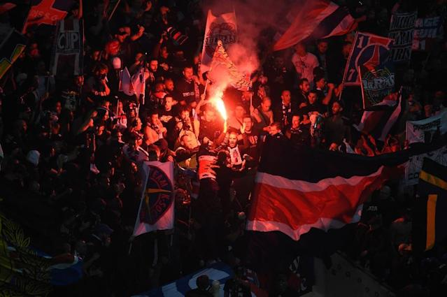 Paris Saint-Germain's supporters hold flags and burn a flare on April 1, 2017, at the Parc Olympique Lyonnais stadium in Decines-Charpieu, near Lyon (AFP Photo/ROMAIN LAFABREGUE)