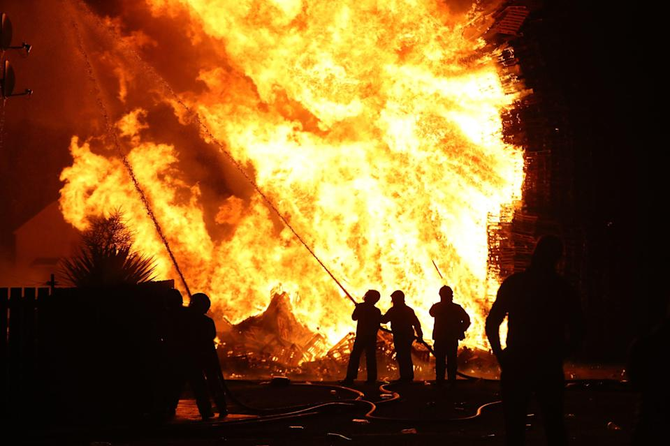 Fire fighters dampen down nearby properties as a huge bonfire in the loyalist Corcrain area of Portadown, Co Armagh, is lit (PA Wire)