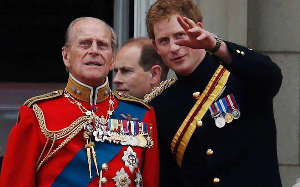 Prince Harry talks to Prince Philip as members of the Royal family appear on the balcony of Buckingham Palace, during the Trooping The Colour parade, in central London in 2014  - AP Photo/Lefteris Pitarakis, File