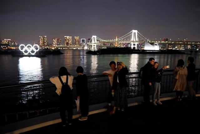People take selfies in front of the giant Olympic rings at the waterfront area at Odaiba Marine Park in Tokyo