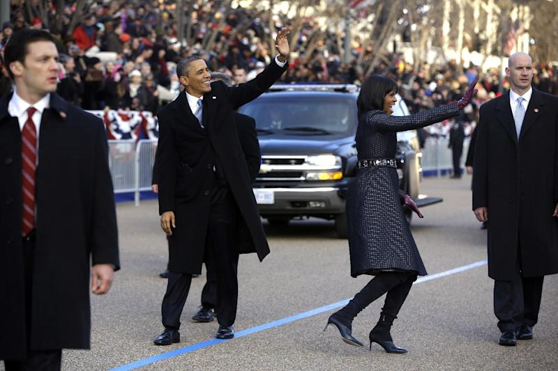 President Barack Obama and first lady Michelle Obama wave as they walk on Pennsylvania Avenue in Washington, Monday,Jan. 21, 2013, in the inaugural parade during the 57th Presidential Inauguration. (AP Photo/Charles Dharapak)