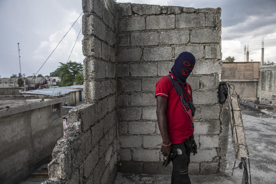 A gang member, wearing a balaclava and holding a gun, poses for a photo in the Portail Leogane neighborhood of Port-au-Prince, Haiti, Thursday, Sept. 16, 2021. There could be as many as 100 gangs in Port-au-Prince; no one has an exact count and allegiances often are violently fluid. (AP Photo/Rodrigo Abd)