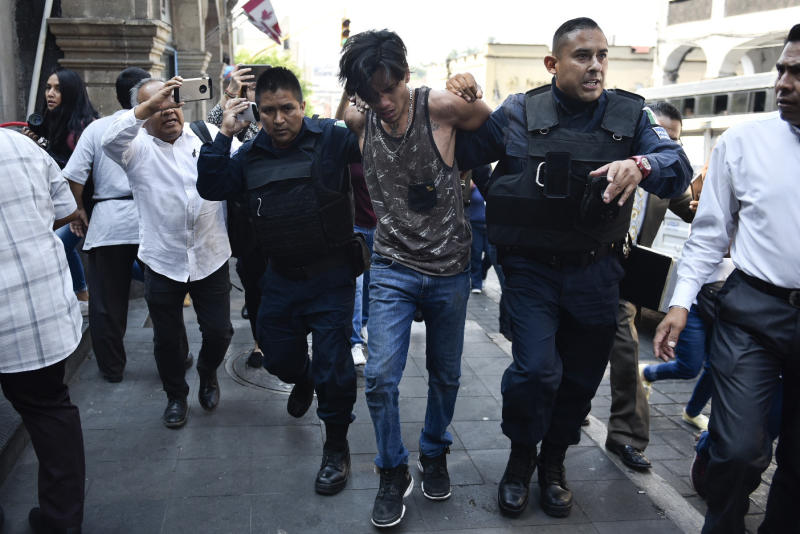 Police arrest a man who started shooting outside City Hall in Cuernavaca, Mexico, Wednesday, May 8, 2019. The man opened fire at the entrance of City Hall where journalists were interviewing government officials, killing two people, including a union member who was apparently with street vendors who were protesting nearby, and injuring two others, according to officials. (AP Photo/Tony Rivera)