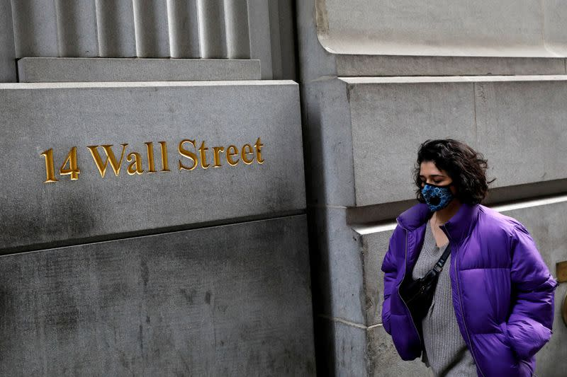 FILE PHOTO: A person wearing a face mask walks along Wall Street after further cases of coronavirus were confirmed in New York City, New York