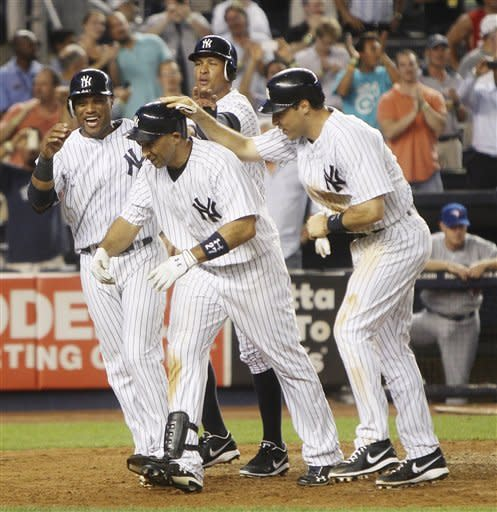 New York Yankees' Raul Ibanez, second from left, is greeted by Robinson Cano, left, Alex Rodriguez, second from right, and Mark Teixeira after he hit a grand slam during the eighth inning of the baseball game against the Toronto Blue Jays Monday, July 16, 2012 at Yankee Stadium in New York. (AP Photo/Seth Wenig)
