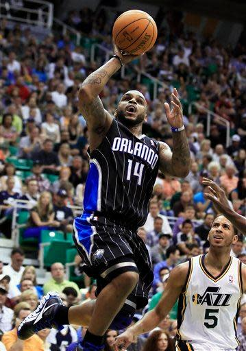 Orlando Magic's Jameer Nelson, left, shoots the ball as Utah Jazz's Devin Harris looks on during the first half of an NBA basketball game in Salt Lake City, Saturday, April 21, 2012. (AP photo/George Frey)