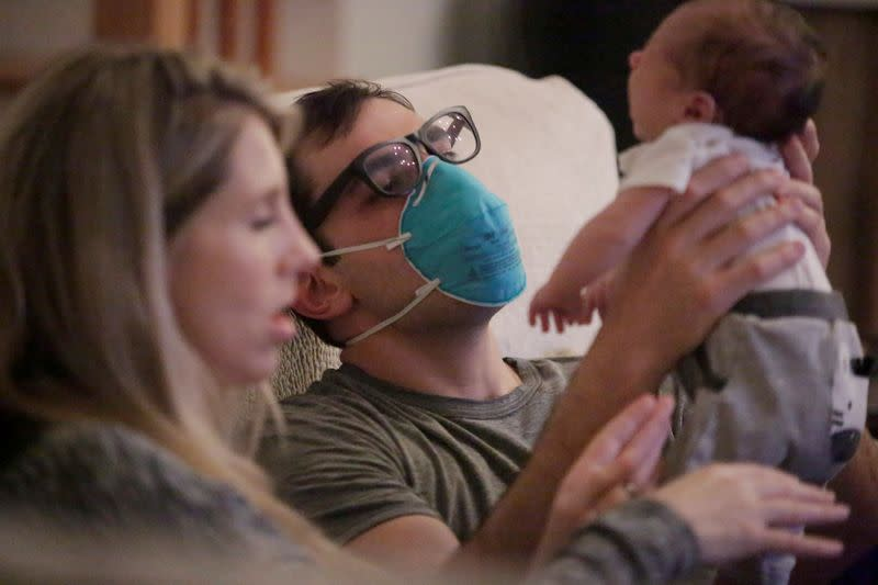 Emergency medicine physician Krajewski wears a mask as he holds his baby in New Orleans