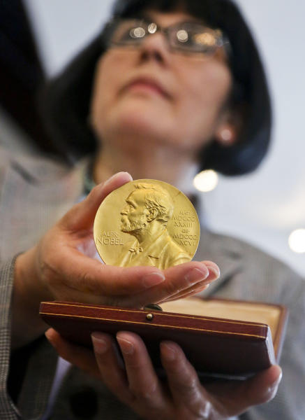 Sandra Palomino, director of historical manuscripts at Heritage Auctions, holds the1962 Nobel Prize for Physiology or Medicine awarded to Dr. Francis Harry Compton Crick, Wednesday, April 10, 2013 in New York. On Thursday, the molecular biologist's medal and accompanying diploma will be sold by Heritage Auctions, which estimates it could fetch at least $500,000. (AP Photo/Bebeto Matthews)