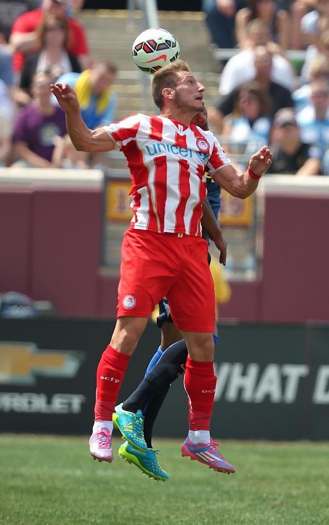 Dimitrios Diamantakos of Olympiacos heads the ball from Manchester City defender Gael Clichy (22) during the first half of the Guinness International Champions Cup at TCF Bank Stadium on the University of Minnesota campus in Minneapolis, Saturday, Aug. 2, 2014.(AP Photo/Andy Clayton-King)