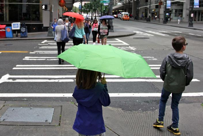 In this Tuesday, June 26, 2012 photo, In this Tuesday, June 26, 2012 photo, a girl waits to cross a downtown Seattle cross walk under the rain. Across the United States, hundreds of heat records have fallen in the past week, but Washington state's largest city has seen lower than average temperatures to kick off summer. (AP Photo/Manuel Valdes)