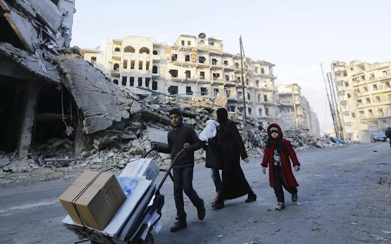 Syrians walk amid destroyed buildings as residents return to Aleppo's formerly rebel-held al-Shaar neighbourhood on January 21, 2017, a month after government forces retook the northern Syrian city from rebel fighters. - Credit: LOUAI BESHARA/AFP or licensors