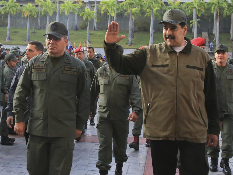 In this photo released by Miraflores Press Office, Venezuela's President Nicolas Maduro, right, accompanied by his Defense Minister Vladimir Padrino Lopez, waves upon his arrival to Fort Tiuna, in Caracas, Venezuela, Thursday, May 2, 2019. The Associated Press has learned that at least twice since 2016, the U.S. government missed chances to cultivate relations with regime insiders, including Padrino, who National Security Adviser John Bolton said backed out of a plan to topple Maduro. (Jhonn Zerpa/Miraflores Press Office via AP)