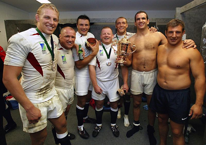 England players (as well as all being Leicester Tigers), from left, Lewis Moody, Neil Back, Martin Corry, Dorian West, Ben Kay, captain Martin Johnson, and Julian White celebrate in the dressing rooms with the William Webb Ellis trophy after their win in the Rugby World Cup final against Australia, in Sydney. England defeated Australia 20-17 in extra time. (Photo by PA Images via Getty Images)