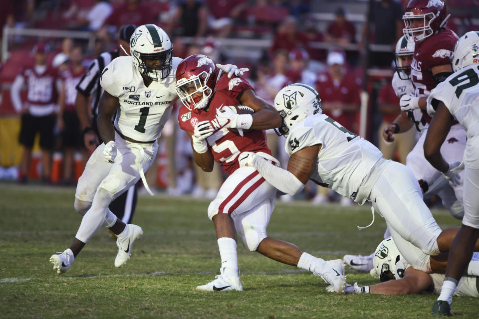 Arkansas running back Rakeem Boyd (5) is taken down by Portland State defenders Romeo Gunt (1) and Kenton Bartlett (51) during the second half of an NCAA college football game Saturday, Aug. 31, 2019 in Fayetteville, Ark. (AP Photo/Michael Woods)
