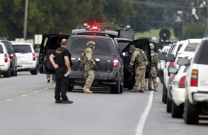 Louisiana state, federal and local law enforcement gather along La. Highway 128 outside a Tensas State Bank branch during a hostage situation in St. Joseph, La., Tuesday, Aug. 13, 2013. A man whose family owns a store across the street from the bank took three bank employees hostage, and a state police negotiator has been talking to him for hours, police said. (AP Photo/Rogelio V. Solis)