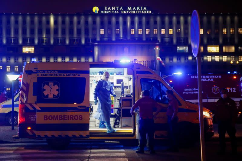Medical personnel stand next to ambulances with COVID-19 patients as they wait in the queue at Santa Maria hospital, amid the coronavirus disease (COVID-19) pandemic in Lisbon