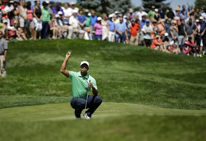Tiger Woods holds a golf ball on the fifth hole as he waits to putt during the third round of The Barclays golf tournament Saturday, Aug. 24, 2013, in Jersey City, N.J. (AP Photo/Mel Evans)