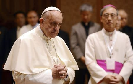 Pope Francis prays as he arrives the headquarters of the Korean Bishops's Conference to attend a meeting with the bishops in Seoul August 14, 2014. REUTERS/Korea Pool/News1