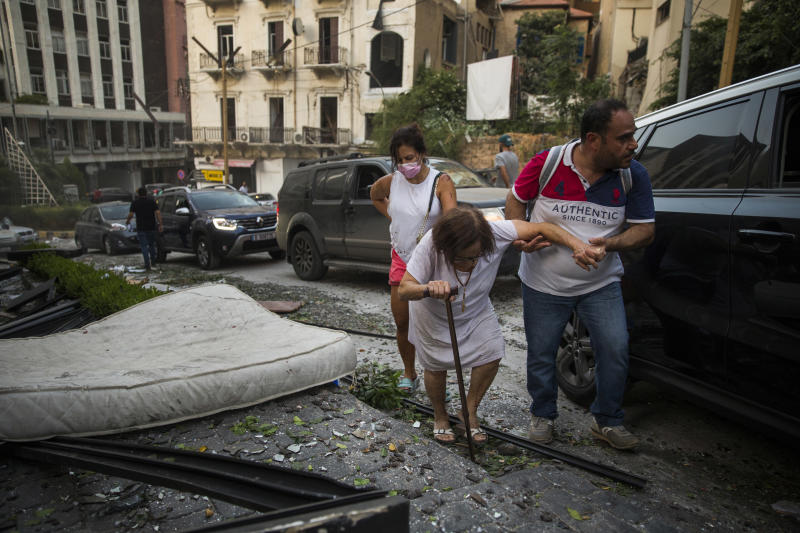 BEIRUT, LEBANON - AUGUST 04: An elderly woman is helped while walking through debris after a large explosion on August 4, 2020 in Beirut, Lebanon. Video shared on social media showed a structure fire near the port of Beirut followed by a second massive explosion, which damaged surrounding buildings and injured hundreds. (Photo by Daniel Carde/Getty Images)