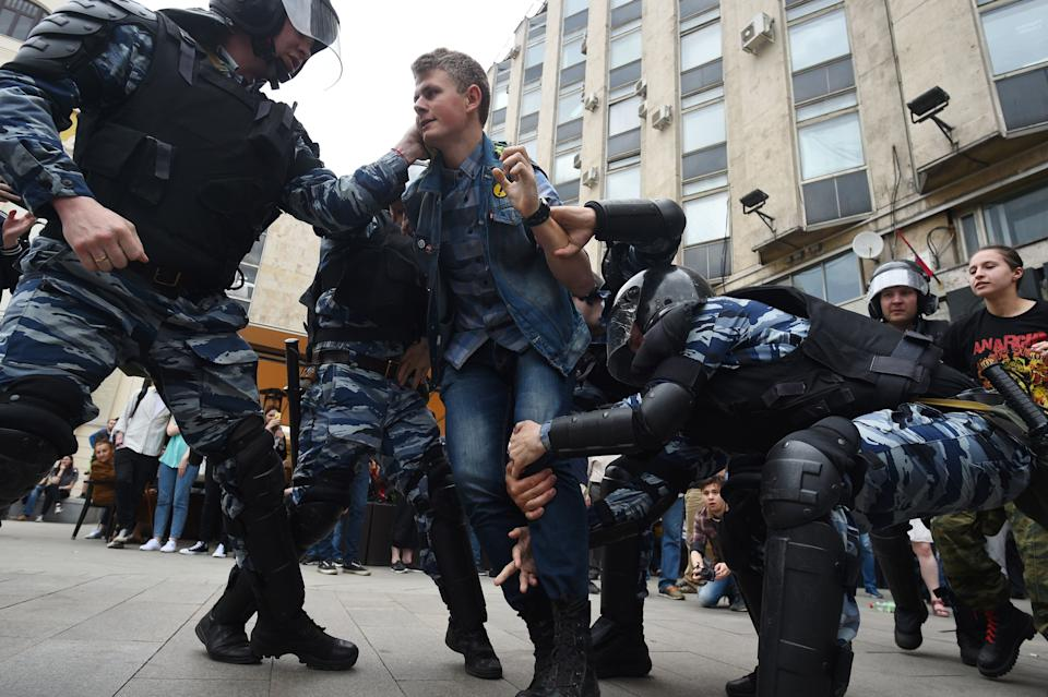 Russian police officers detain a participant.