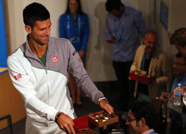 Novak Djokovic of Serbia hands out chocolate to reporters during a press conference ahead of the Australian Open tennis championship in Melbourne, Australia, Sunday, Jan. 12, 2014. (AP Photo/Shuji Kajiyama Shuji)