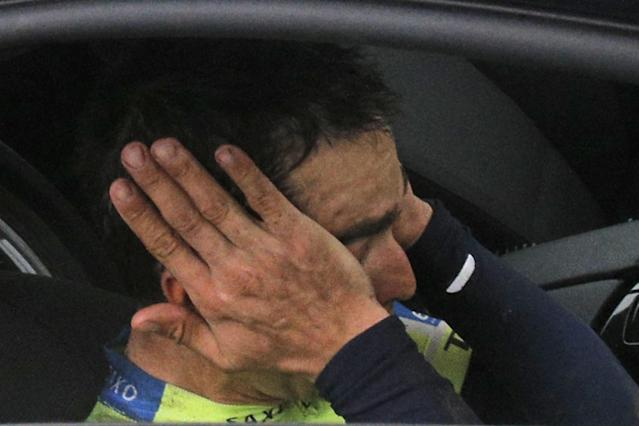 Spain's Alberto Contador covers his face as he abandons the race after crashing during the tenth stage of the Tour de France cycling race over 161.5 kilometers (100.4 miles) with start in Mulhouse and finish in La Planche des Belles Filles, France, Monday, July 14, 2014. (AP Photo/Christophe Ena)