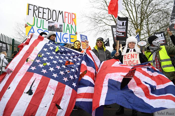Supporters of WikiLeaks founder Julian Assange hold U.S. and U.K. flags and placards calling for his freedom outside Woolwich Crown Court in southeast London on Feb. 24, 2020.
