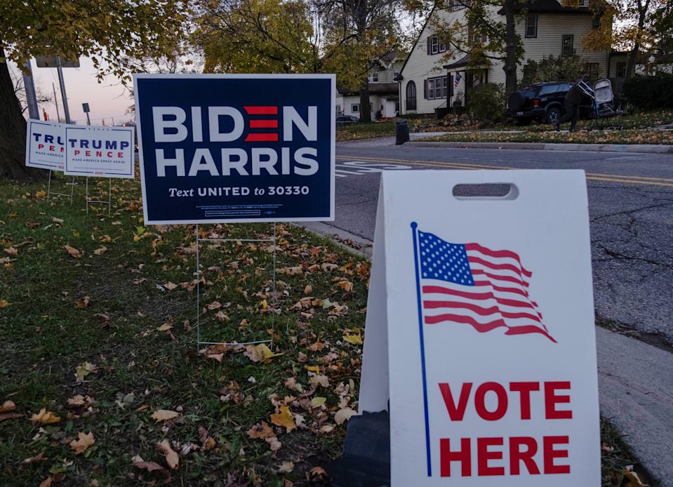 """Trump and Pence signs and Biden, Harris signs are seen near Eisenhower Elementary School a polling area in Flint, Michigan on November 3, 2020. - The US is voting Tuesday in an election amounting to a referendum on Donald Trump's uniquely brash and bruising presidency, which Democratic opponent and frontrunner Joe Biden urged Americans to end to restore """"our democracy."""" (Photo by Seth Herald / AFP) (Photo by SETH HERALD/AFP via Getty Images)"""
