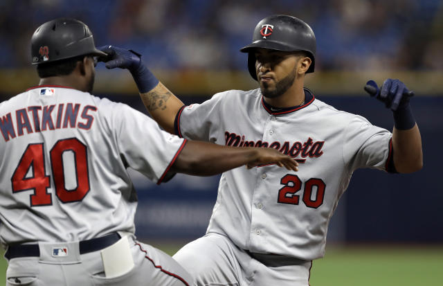 Minnesota Twins' Eddie Rosario (20) celebrates his two-run single off Tampa Bay Rays relief pitcher Adam Kolarek with first base coach Tommy Watkins during the ninth inning of a baseball game Friday, May 31, 2019, in St. Petersburg, Fla. (AP Photo/Chris O'Meara)