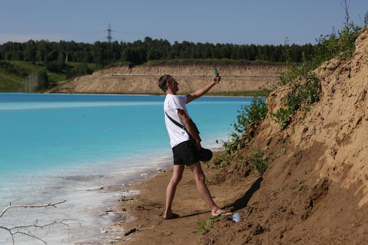 """A man takes a selfie picture by a Novosibirsk energy plant's ash dump site - nicknamed the local """"Maldives"""" - on July 11, 2019. (Photo: Rostislav Netisov/AFP/Getty Images)"""