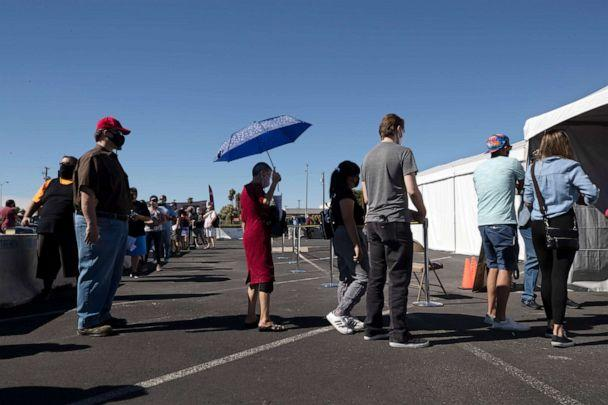 PHOTO: In this Oct. 17, 2020 file photo a woman uses an umbrella for shade as voters line up at an early voting site during the first day of early voting in Las Vegas.  (Steve Marcus/AP)