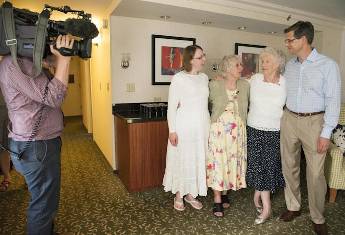 A television crew from the BBC, left, records the May 1, 2014 reunion at the Fullerton Marriott of twin sisters Ann Hunt and Liz Hamel, both 78, in Fullerton, Calif. Pictured, from left, are Samantha Stacey, her mother Ann Hunt, Liz Hamel, and her son, Quinton Hamel. Hunt and Hamel are considered the world's longest-separated twins. (AP Photo/Orange County Register, Leonard Ortiz) MANDATORY CREDIT, LEONARD ORTIZ, ORANGE COUNTY REGISTER