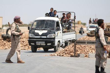 Syria Democratic Forces (SDF) fighters man a checkpoint as civilians on pick-up trucks evacuate from the southern districts of Manbij city after the SDF advanced into it in Aleppo Governorate