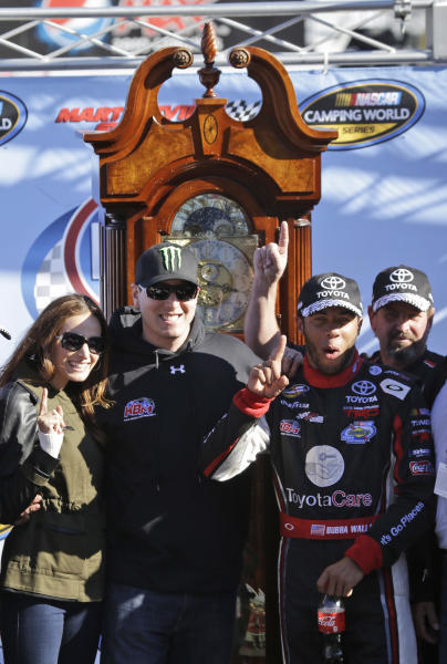 Darrell Wallace Jr., second from right, celebrates in Victory Lane with team owner Kyle Busch, second from left and Busch's wife Samantha, after winning the NASCAR Truck Series truck race at Martinsville Speedway in Martinsville, Va., Saturday, Oct. 26, 2013. The grandfather clock trophy is in the background. (AP Photo/Steve Helber)