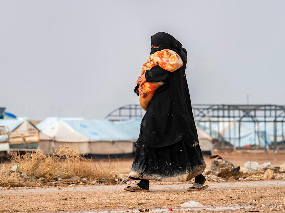A woman carrying a toddler walks at the Kurdish-run al-Hol camp for the displaced where families of Islamic State (IS) foreign fighters are held, in the al-Hasakeh governorate in northeastern Syria on 9 December 2019 (AFP via Getty Images)