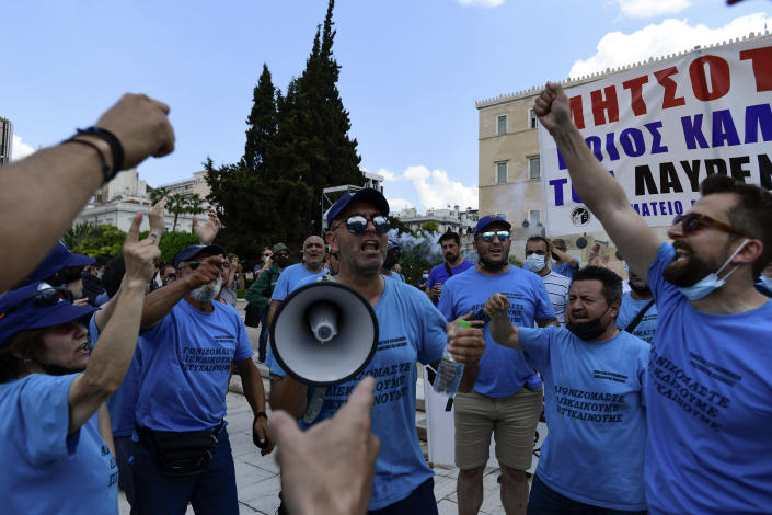 Protesters shout slogans as they take part in a rally during a 24-hour labor strike, in Athens, Thursday, June 10, 2021. Widespread strikes in Greece brought public transport and other services to a halt Thursday, as the country's largest labor unions protested against employment reforms they argue will make flexible workplace changes introduced during the pandemic more permanent. (AP Photo/Michael Varaklas)