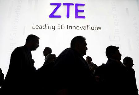 FILE PHOTO - Visitors pass in front of the Chinese telecoms equipment group ZTE Corp booth at the Mobile World Congress in Barcelona, Spain, February 26, 2018. REUTERS/Sergio Perez/File Photo
