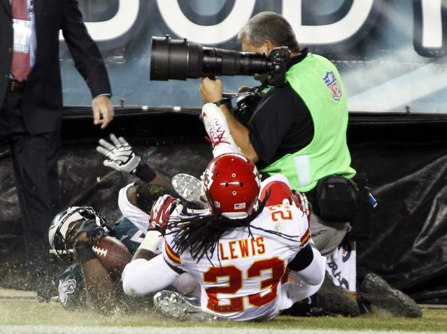 Philadelphia Eagles' LeSean McCoy (25) and Kansas City Chiefs' Kendrick Lewis (23) roll into a photographer on the sidelines after McCoy scored a touchdown during the fourth quarter of their NFL football game in Philadelphia, Pennsylvania, September 19, 2013. Kansas City won 26-16. REUTERS/Tom Mihalek (UNITED STATES - Tags: SPORT FOOTBALL)