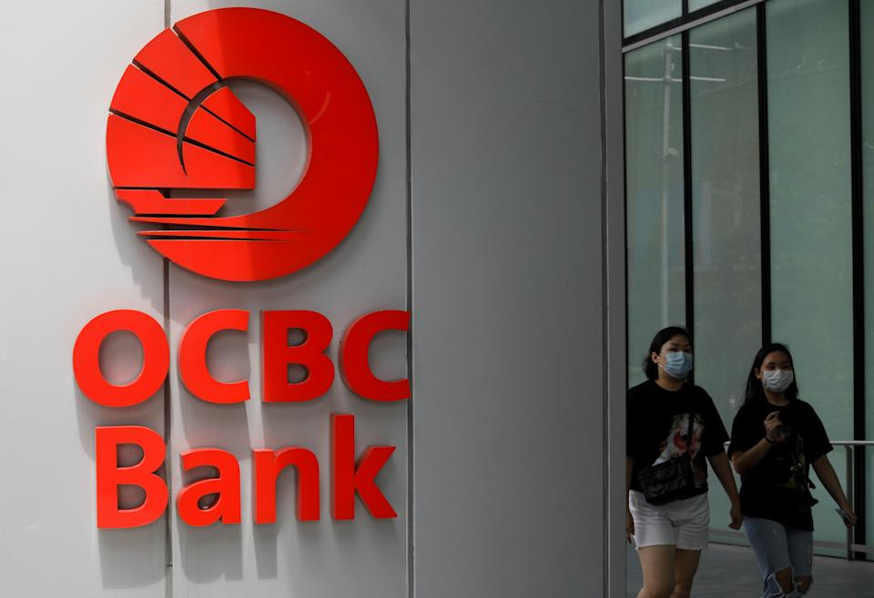 People wearing protective face masks pass an OCBC bank signage during the coronavirus disease (COVID-19) outbreak in Singapore, August 17, 2020.   REUTERS/Edgar Su
